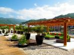 Rooftop shared gazebos apointed with sofas, tables and chairs, fan and lighting