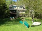 Waterside View of House Facing Lake with Canoe and Kayak