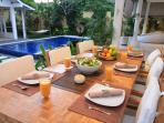 open air dining area overlooking swimming pool and lush garden.