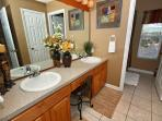 Hall Bathroom with separate water closet and twin vanities, as well as separate room for bathtub.