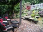 Cobblestone patio with shaded sitting area and BBQ just outside of kitchen - lounging/eating space