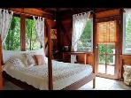 Master bedroom next to 1rst bathroom . Door to Sunny East deck
