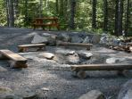 Fire pit, picnic table and woods behind the lodge