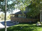 Exterior view with beautifully landscaped grounds, large aspens