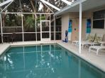 Oversized screened in private pool area overlooks the private fenced in yard and foliage.