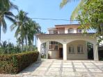The house is Mediterranean style; its doors are wooden and the garage is roofed for two cars.