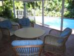 Patio area has pool table, fooseball table & large tropical sitting area by pool