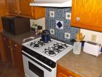 COOKING AREA SHOWING STOVE W/HOOD AND MICROWAVE ON COUNTER