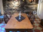 Dining room with stenciled floor, stone wall and fireplace