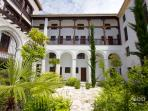 The plant-filled central courtyard of the building with traditional architectural features.