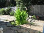 Side patio and small pond.