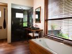 Bathroom with bathtub, twin washing basins, separate shower and private toilet