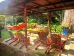 The front patio is equipped with lounge chairs, picnic table, and hammock.