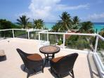 Ocean view roof deck with lounge chairs and patio set