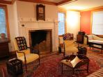The living room has a fireplace, plenty of seating, a stereo, jigsaw puzzles, and other games