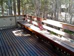 Redwood deck with built-in bench and BBQ runs the width of the home, with views of trees and pond.