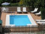 Piscina, terraza, tumbonas, y mesa para disfrutar del sol