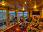 Family room looks out wall of windows onto the lake and has pellet stove
