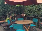 Redwood Deck with tables, umbrella, chaise lounges