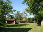 There is a large grassy farmyard area with swings and out-buildings