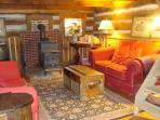 Inviting LRm with 2 love seats, a wood stove & antiques