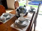 Dining table set for four, with 2 extra settings and chairs to accommodate 6 people