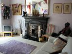 The bright living room has a gas fire and a comfortable double sofa bed.