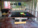 Ping pong table with paddles and balls on screened porch