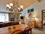 Living room with gas fireplace, flat screen television, and dining area with seating for 6