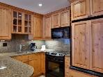 Fully equipped kitchen with additional breakfast bar seating.