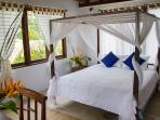 bedroom with a comfortable double bed with mosquito net and AC