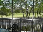 screened balcony morning sun patio furniture looks to 15th fairway Greg Norman course