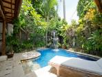 plunge pool with waterfall and jacuzzi and sunbeds