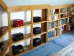 Antique clock radios and many books in master bedroom.