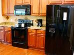 Picture of new cabinets, new electric stove and refrigerator along with new microwave