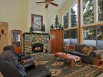 The living room upstairs has a stone fireplace, a comfy couch and a peaceful view