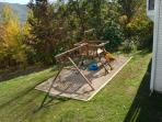 Back yard with playground and fire pit.