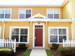 Adorable yellow exterior with white picket fence