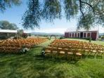 chairs set up in picnic area/soccer field for a wedding.