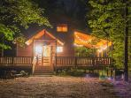 Night time view of The Bear Affair with outside living space and hot tub area lit up