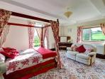 This spacious master bedroom has windows to two sides, with lovely views