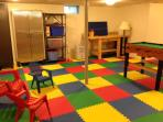 Basement with play area and cabinet with toys and sports