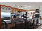 Gourmet kitchen with high end appliances and bar seating for 3 is fully equipped for your culinary needs.