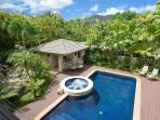 Blue tiled pool and hot tub surrounded by waterfalls in lush, private backyard.
