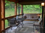 Screened porch: dining table, loveseats, chairs that rock; patio lights; padded porch swing/futon