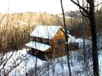 West ledge view of log home in winter.