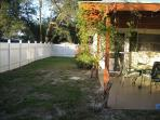 Fenced in back yard with patio covered by pergola