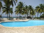 Large swimming pool with spacious sun deck and poolside Beach Shack bar