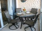Screened back patio includes dining set with seating for four