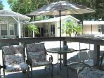 Shaded front porch with umbrella and padded chairs